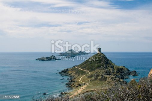 Tiny island in Ajaccio (Corsica) with a lighthouse in the background and a ancient tower in the foreground
