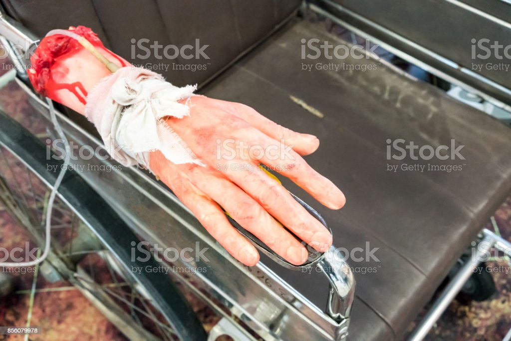 Bloody and creepy halloween toy, fake human hand tied with saline drip on wheel chairBloody and creepy halloween toy, fake human hand tied with saline drip on wheel chair stock photo