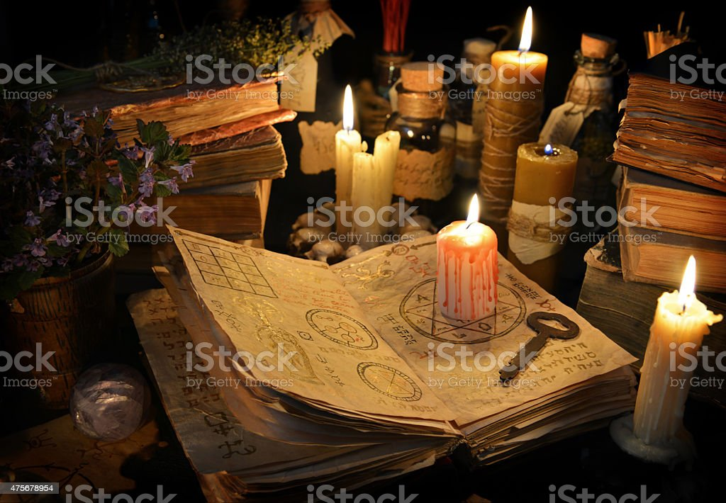 Bloody candle with rustic key on witch book in candle light stock photo