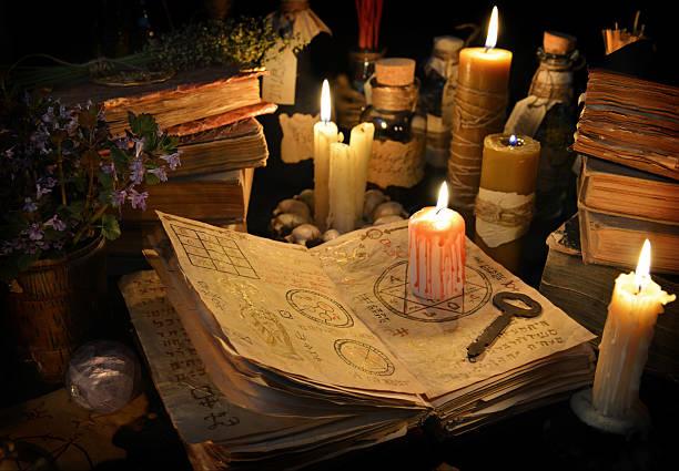 кровавая свеча с грубой ключ на ведьма книгу в при свечах - традиционная церемония стоковые фото и изображения