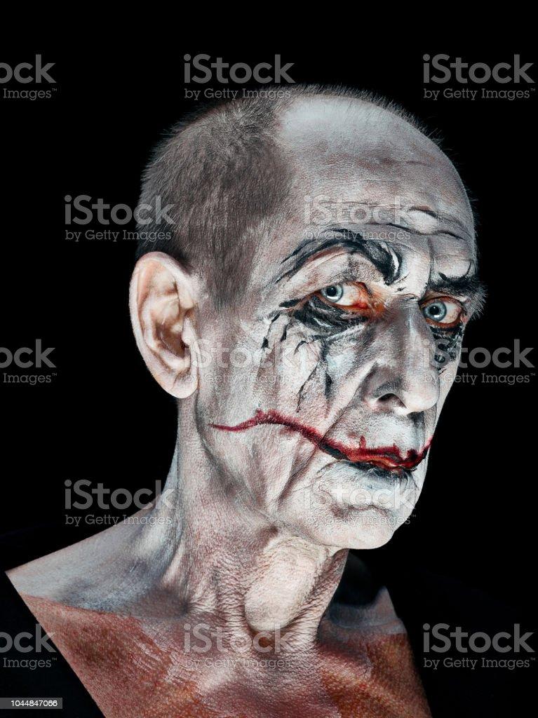 The crazy maniak face on dark studio background
