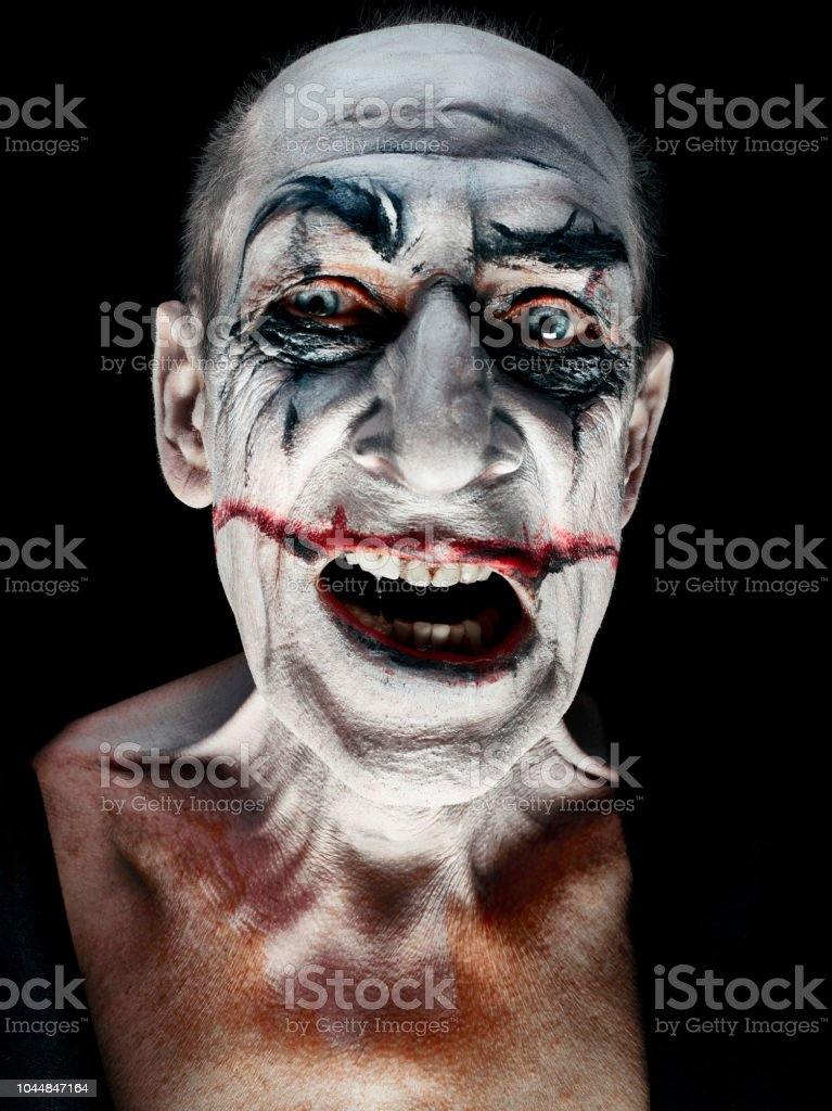 The crazy smiling maniak face on dark studio background