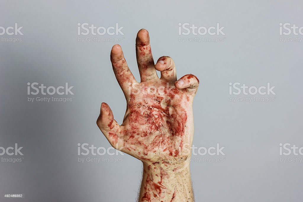bloody hand in front of grey background stock photo