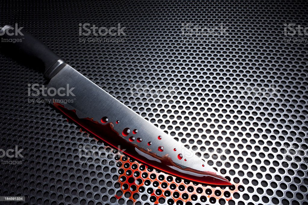 Bloody Kitchen Knife on a Metal Grate stock photo