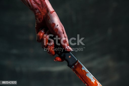 istock Bloody knife. Hand holds a bloody knife 892042520