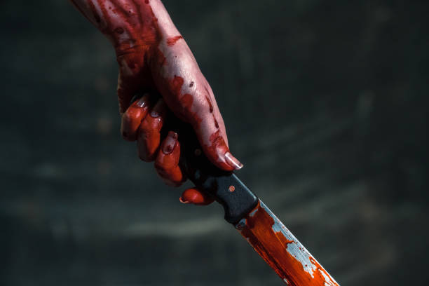 Bloody knife. Hand holds a bloody knife stock photo
