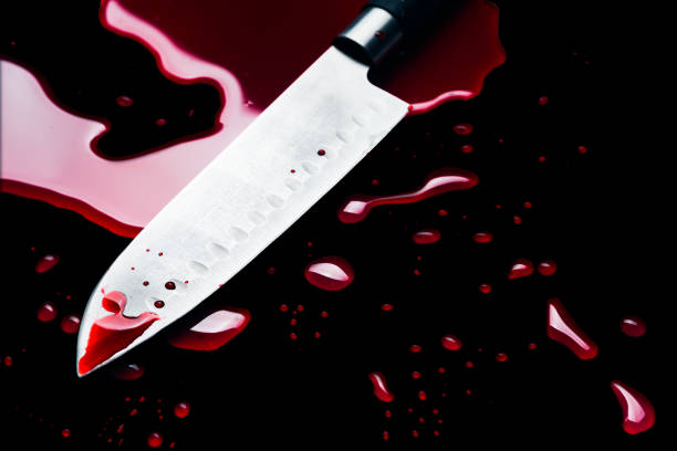 Bloody knife on black background stock photo