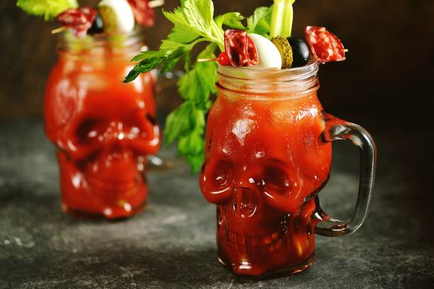 Bloody Mary cocktail in glass skull with celery sticks, pink salt, lime and canapes from canned vegetables. Halloween drink. stock photo
