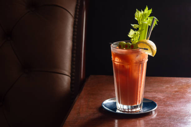 Bloody Mary Cocktail in Glass with Garnish of Olives, Celery, and Lemon in Dark Luxurious Bar stock photo