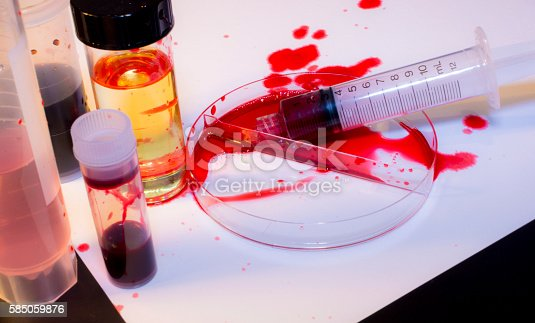 A bloody mess in a laboratory with test tubes, petri dish, syringe. Biohazard.