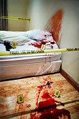 Shot of a cordoned off bedroom crime scene splattered with blood