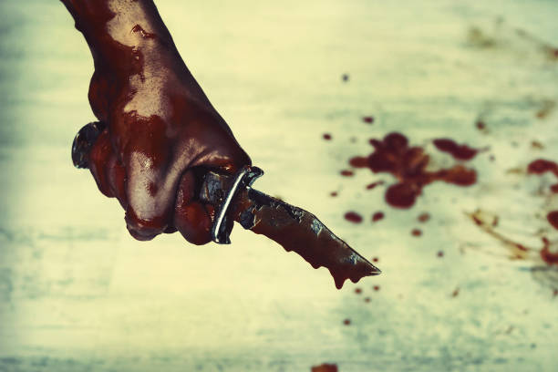 Bloody stabbing. Hand with knife knife, horror blood. Edged weapons in the hand of the Slayer stock photo
