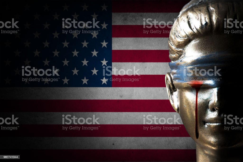 Bloody tear of Lady Justice on U.S.A. flag background (Concept of injustice) stock photo