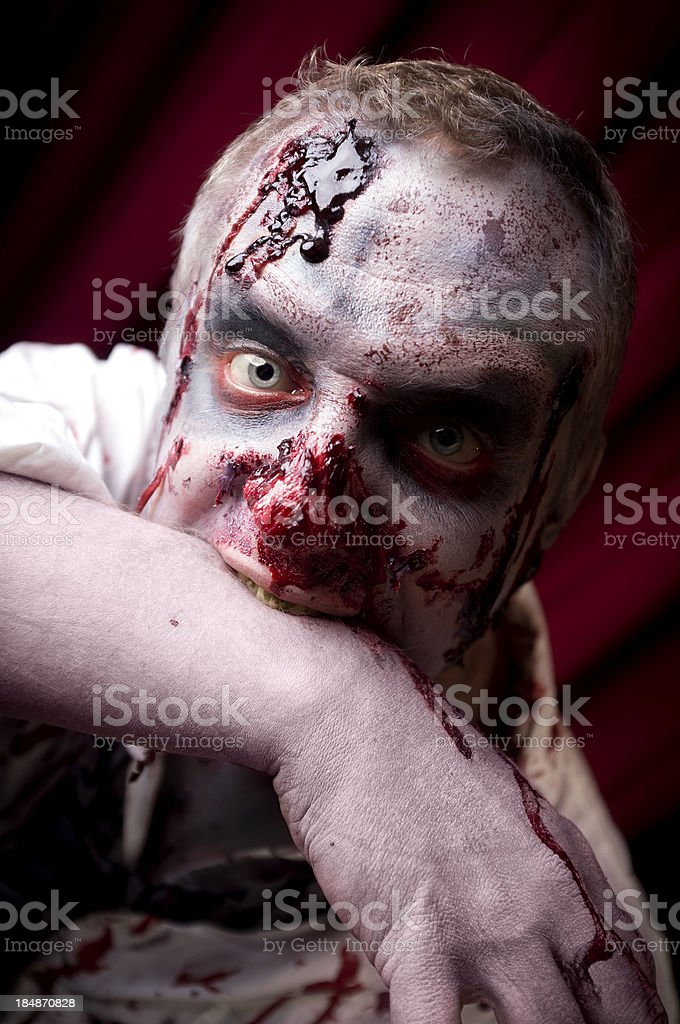 Bloody Zombie Eating His Arm royalty-free stock photo