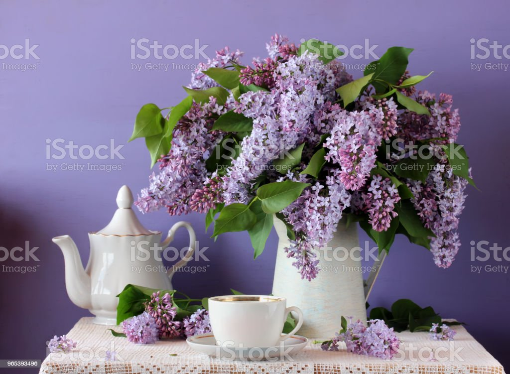 Blooming purple lilac in a jug, Cup and teapot. Still life in rustic style. zbiór zdjęć royalty-free
