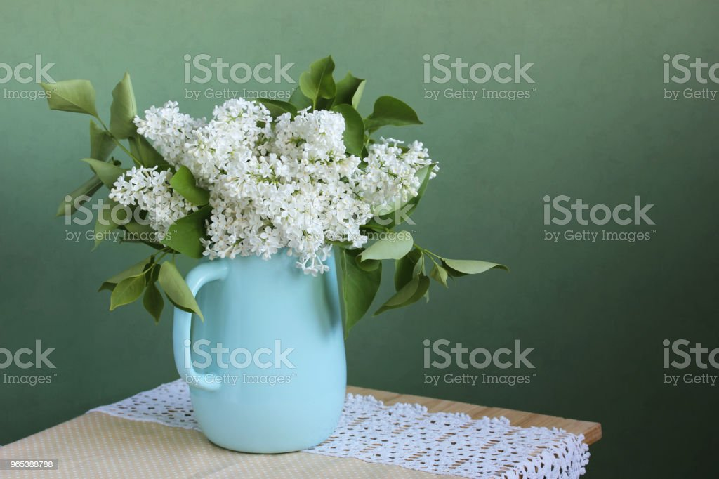 Blooming white lilac in a jug. copy space. royalty-free stock photo