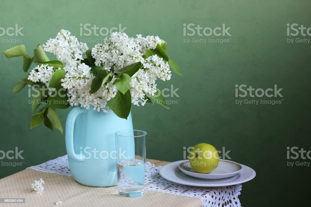 Blooming white lilac in a jug. Still life in rustic style. royalty-free stock photo