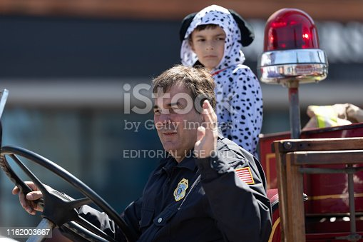 Benton Harbor, Michigan, USA - May 4, 2019: Blossomtime Festival Grand Floral Parade, Man driving an antique St Joseph firetruck during the parade