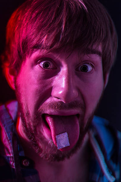 LSD blotter on the tongue stock photo