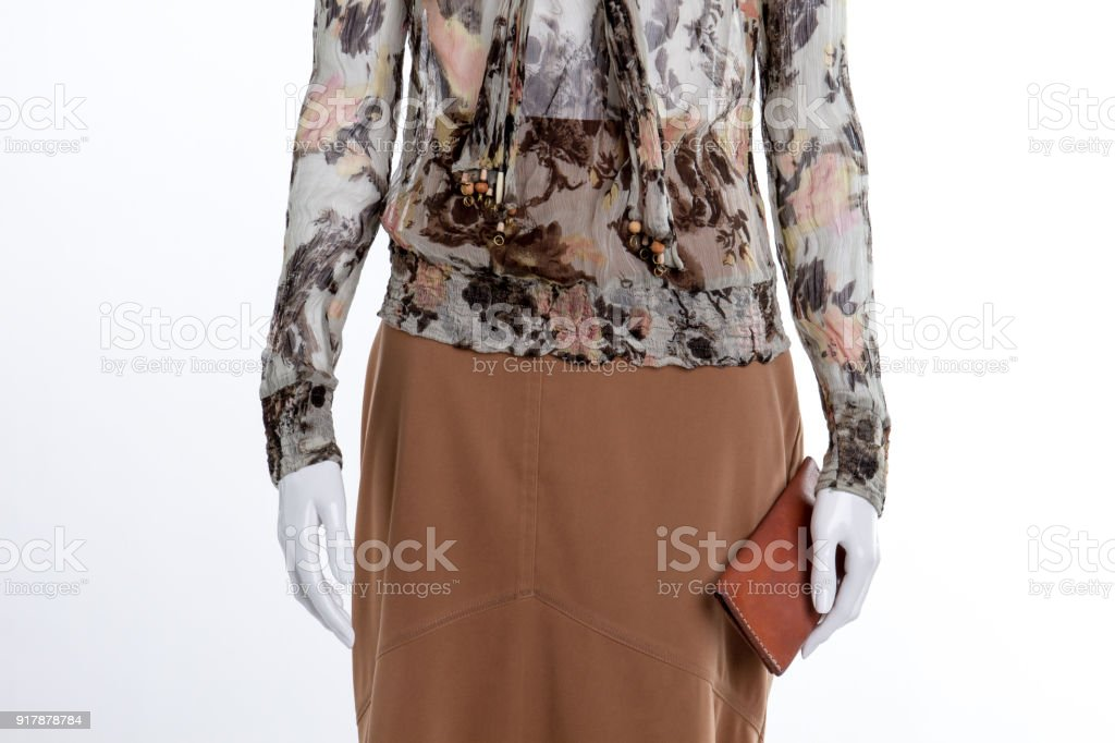 Blouse, brown skirt and wallet close up.