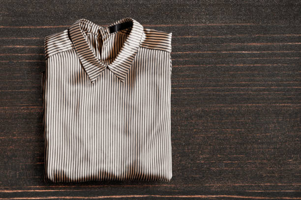 Blouse on wooden background Folded striped satin blouse on dark wooden background blouse stock pictures, royalty-free photos & images