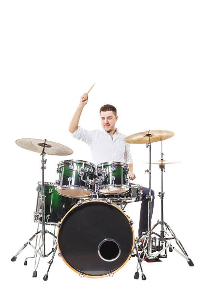 Blow to the plate Handsome guy behind the drum kit on a white background in shirt and trousers drummer stock pictures, royalty-free photos & images