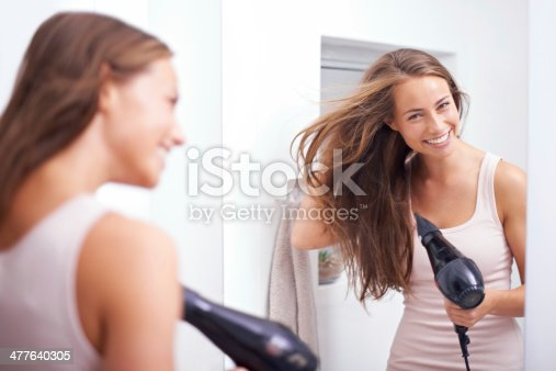 A young woman blow drying her hair in front of a mirror