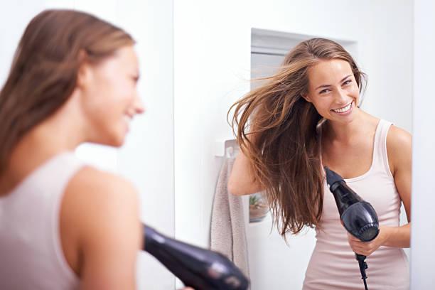 blowdrying her hair - 護髮用品 個照片及圖片檔
