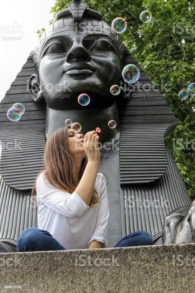 Blowing bubbles in the arms of the Sphinx Bulgarian outdoor girl stock photo