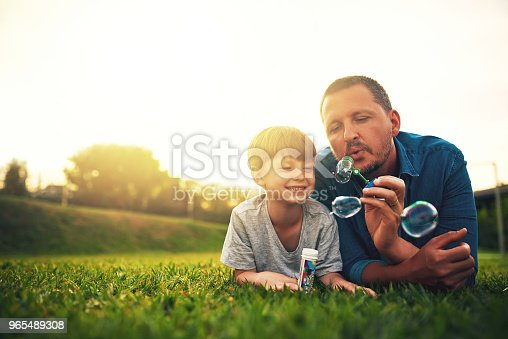 Shot of a father and his adorable son blowing bubbles in the backyard