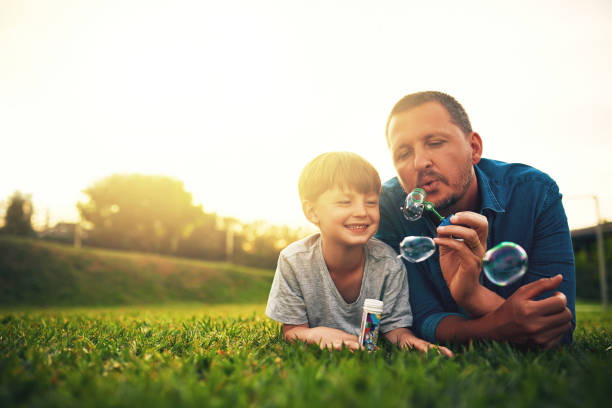 Blowing bubbles in the backyard is my favourite Shot of a father and his adorable son blowing bubbles in the backyard one parent stock pictures, royalty-free photos & images