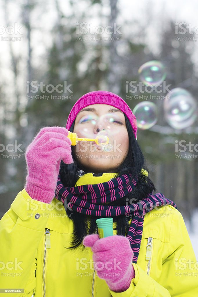 Blowing bubbles in winter forest royalty-free stock photo