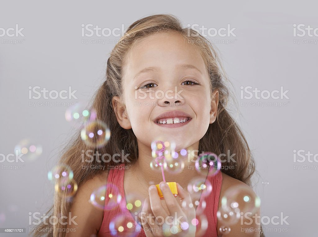 Blowing bubbles An adorable little girl surrounded by bubbles 8-9 Years Stock Photo