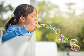 Young girl blowing bubbles outdoors on a terrace. Side view.