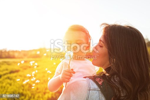 Smiling mother and her baby girl on a field on a bright sunny day. They are blowing dandelion.