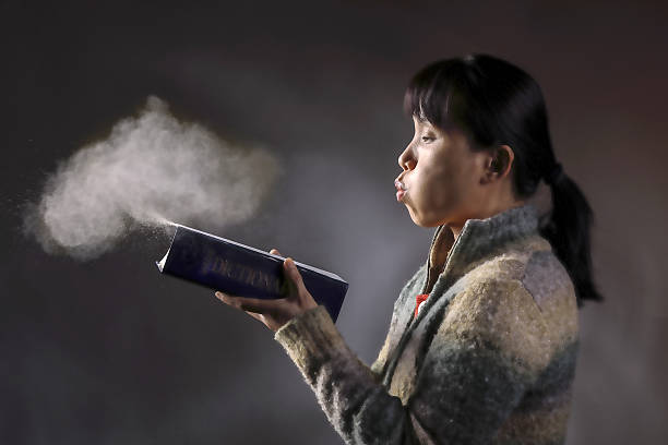 Blowing dust off a book. stock photo