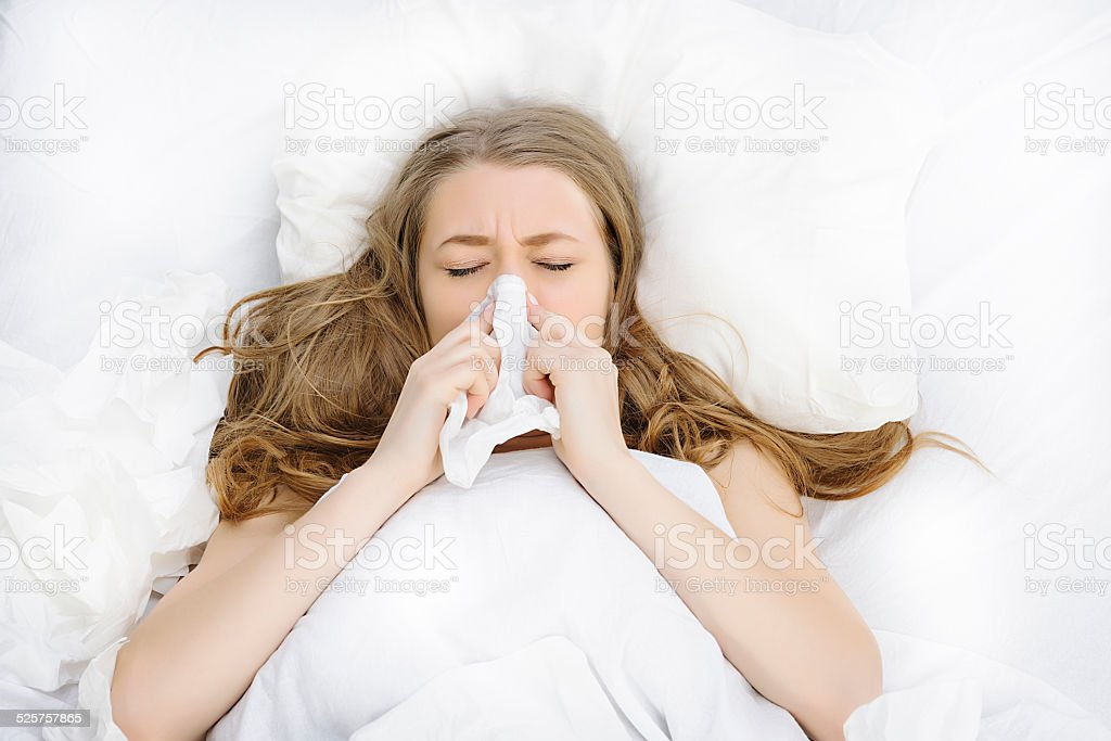 blowing nose in bed stock photo