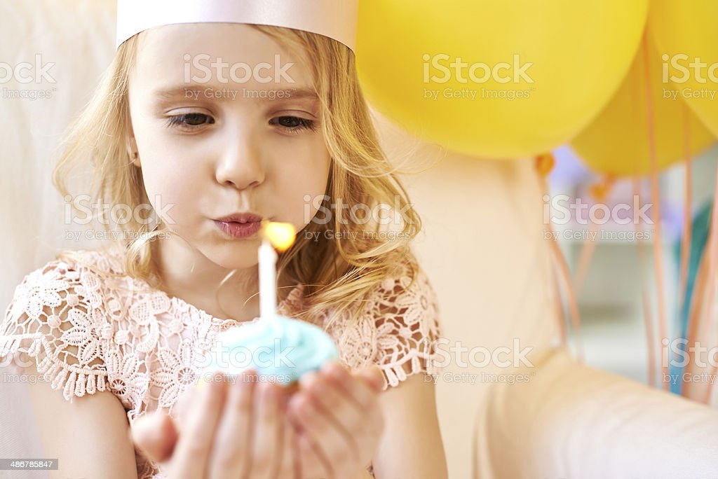 Blowing out birthday candle stock photo