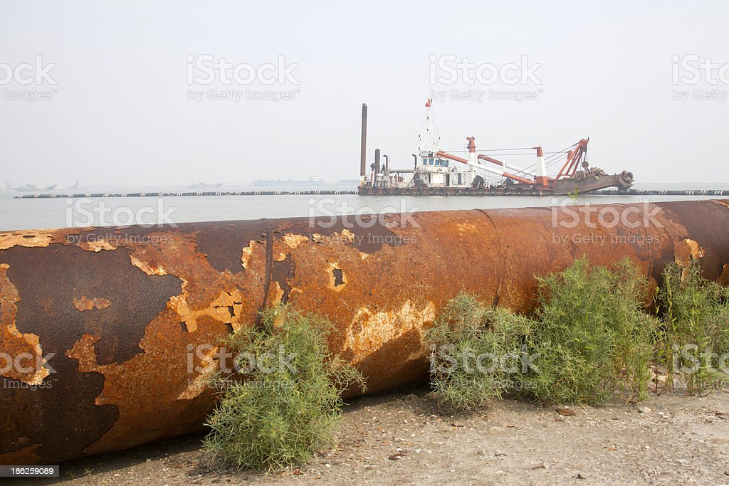 blowing sand pipe and ships in the sea royalty-free stock photo