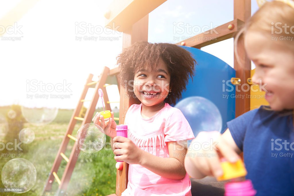 Blowing soap bubble with the best friend stock photo
