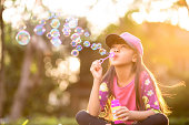Little asian girl blowing soap bubbles outdoor at sunset