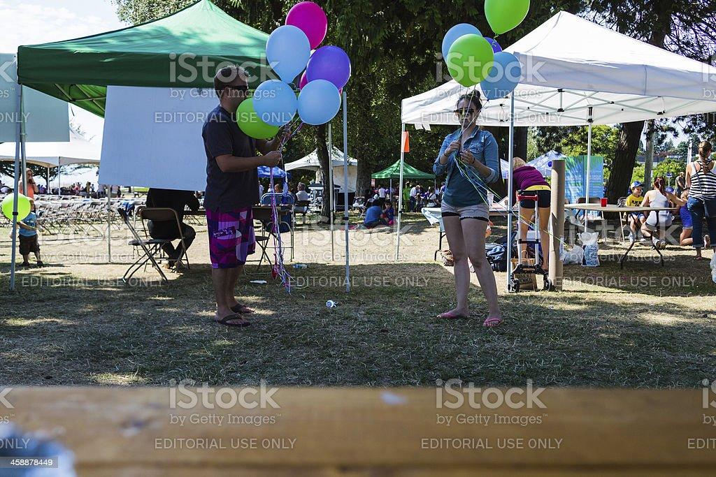 blowing up balloons at harmony arts festival stock photo