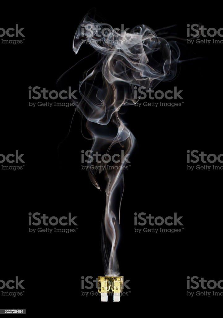 Blown automotive fuse with feminine smoke on black background stock photo