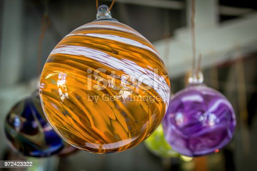 Blow glass floats hang from a ceiling to catch the morning light