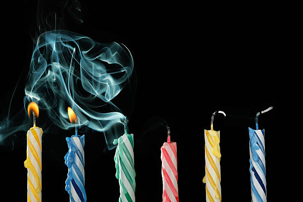 blown out candles birthday candles that have just been blown out with smoke on black background birthday candle stock pictures, royalty-free photos & images