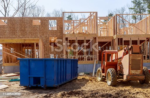 istock Blu dumpster, recycle waste and garbage bins near new construction site of appartment houses building 1148540899
