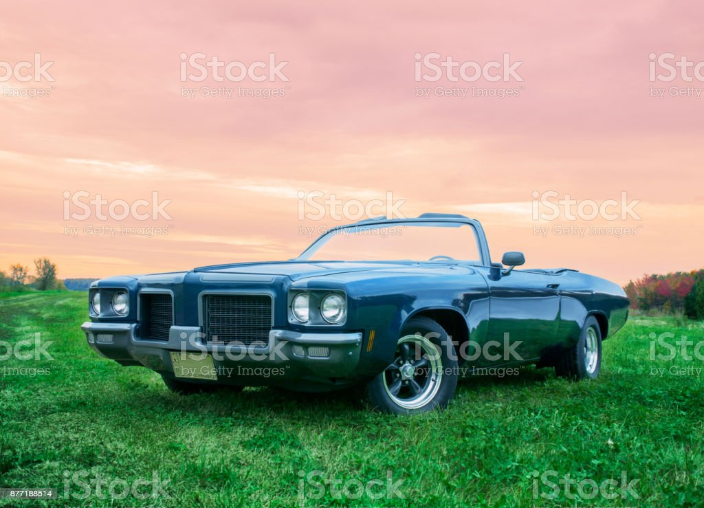 Blue 1971 car parked at sunset stock photo