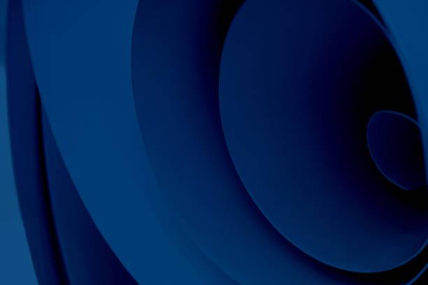 Blauer abstrakter Hintergrund aus wirbelndem Material. Foto von mehreren Blechen, die zu einer Rolle gebogen wurden. – Foto