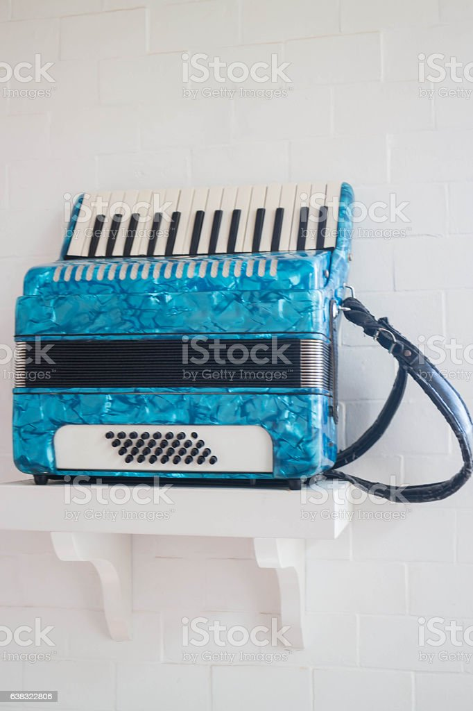 Blue accordion in white room stock photo