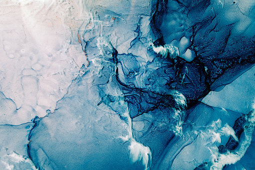 Blue acrylic ink. Marble texture. Frozen water surface with white snow effect. Fractured crystal ice rock abstract design. Mineral stone stained pattern. Nature art background.
